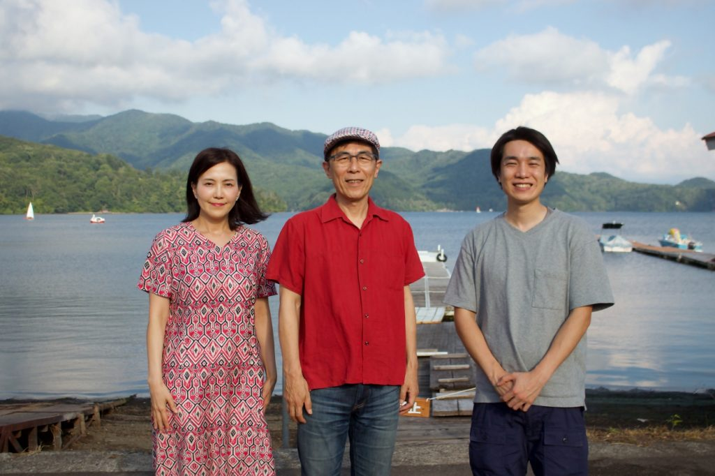 野尻湖をバックに並ぶ、ライターの北尾トロさん、LIGの編集者の平林享子と中野慧