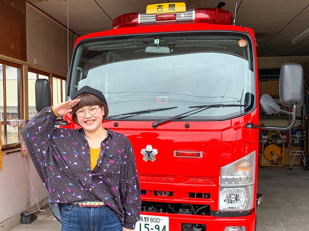 消防車の前に立つ女性