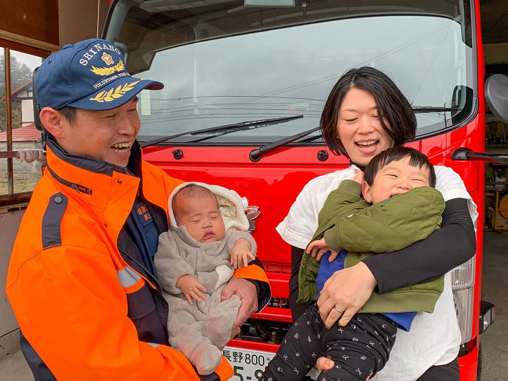 消防車の前で消防団のご夫婦と赤ちゃん