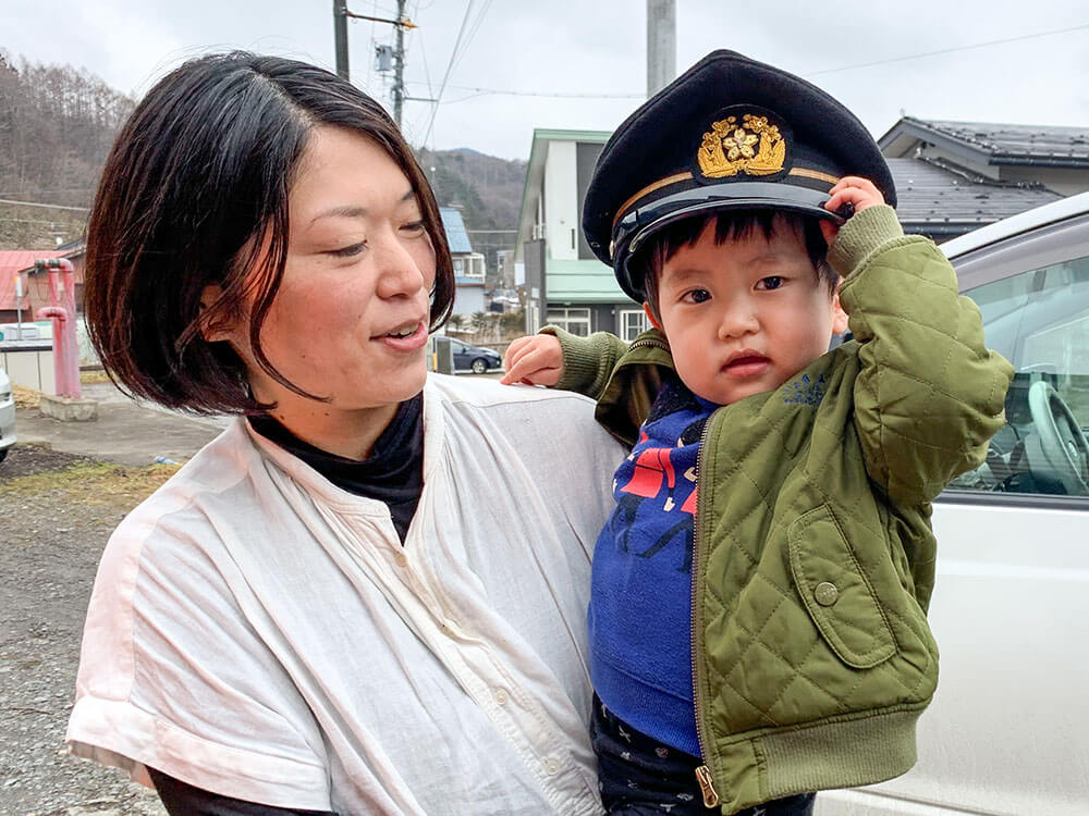 消防団の帽子をかぶる男の子と母親