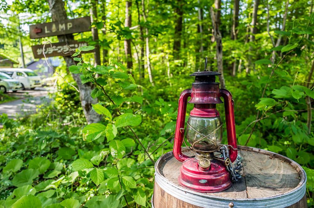 森の中のゲストハウスLAMPの標識と、樽の上に置かれたランタン