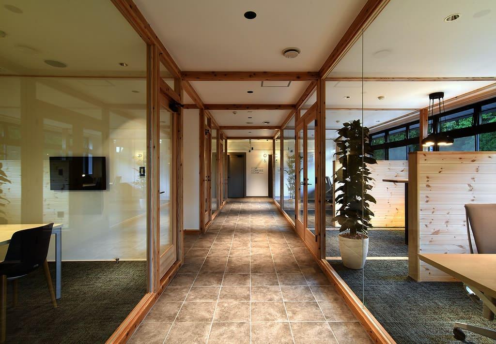 長野県信濃町のノマドワークセンターの内部。オフィスの壁がガラス張りになっていて、外の森が見える