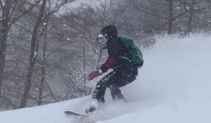 飯田さんがスノーボードをしているところ