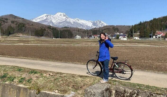 飯田さんの奥さんが自転車から降りて手を振っている。その奥には雪山が見える。