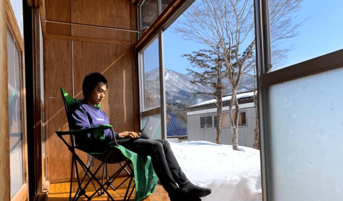 長野県信濃町に購入した古民家の縁側で、キャンプチェアに座り、パソコンに向かっている飯田さん。