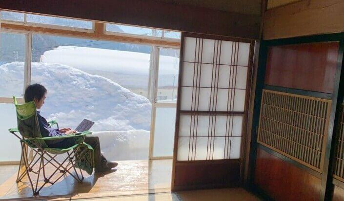 庭に積もった雪を見ながら、縁側で仕事をする飯田さん