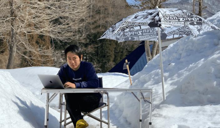 雪が積もった庭にテーブルを出して仕事している飯田さん