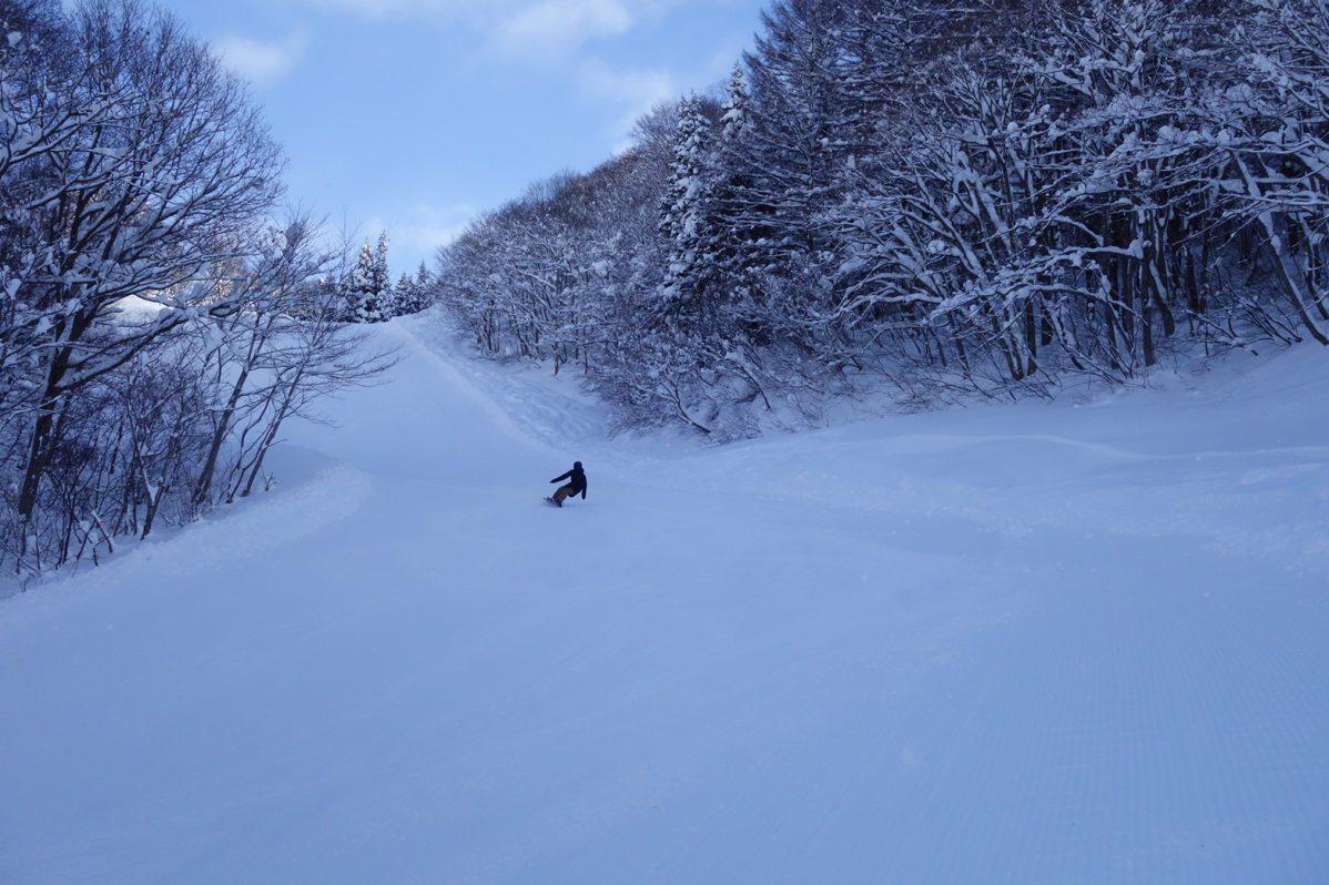 ゲレンデでスノーボードをする姿。