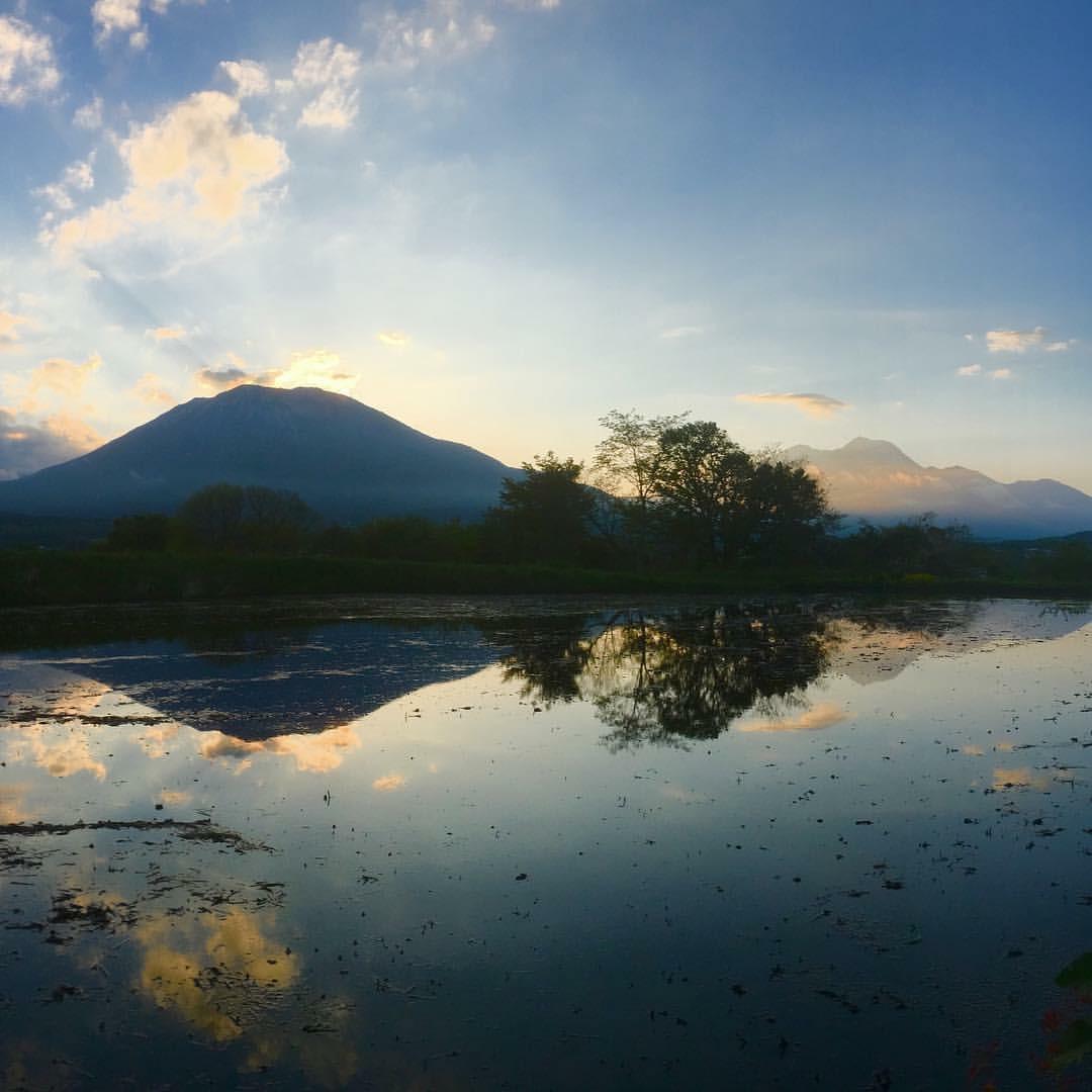 夕暮れの黒姫山と水を張った田んぼ。田んぼに黒姫山と夕空が反射して鏡のようになっている。