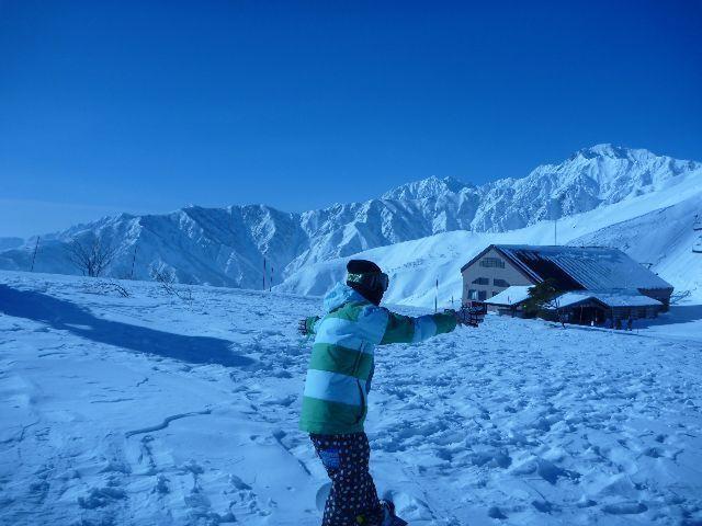 晴天のゲレンデ山頂で、青い空と真っ白い雪山を背景に記念撮影。雪を被った冬の山は、凹凸がはっきり見える。