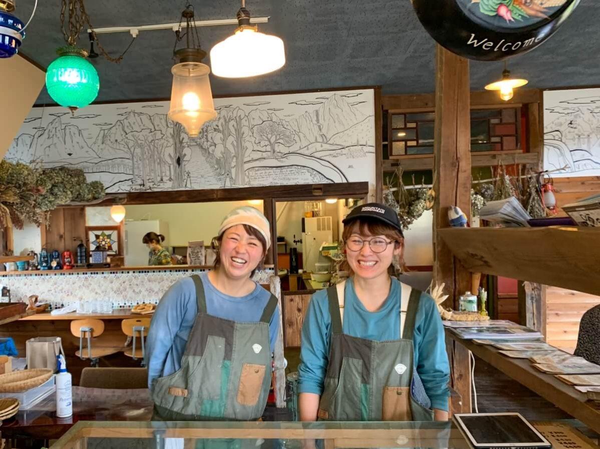 長野県信濃町のベーカリーカフェ「たねcafe  革工房種」店主の大日向さんとスタッフが楽しそうに笑顔で接客しているところ