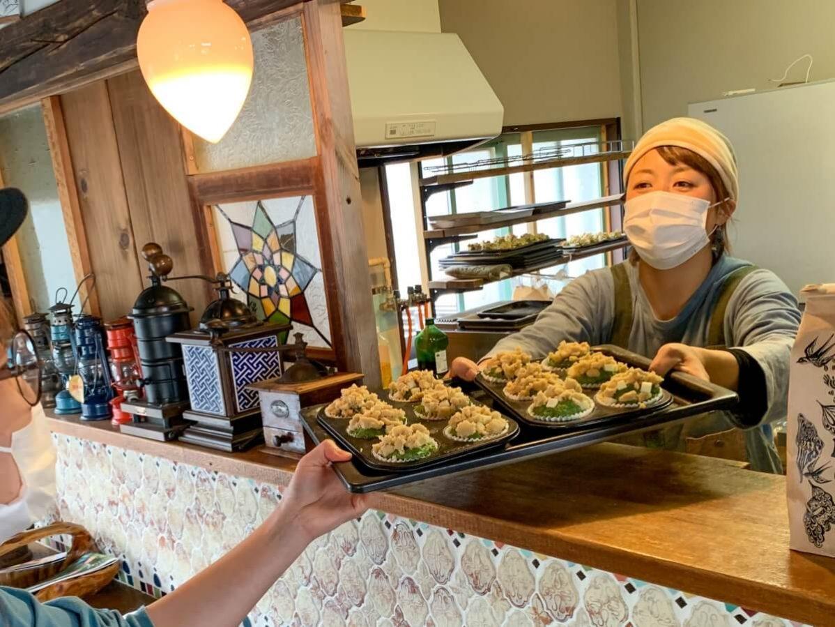長野県信濃町のベーカリーカフェ「たねcafe  革工房種」で、店主の大日向さんが作業しているところ