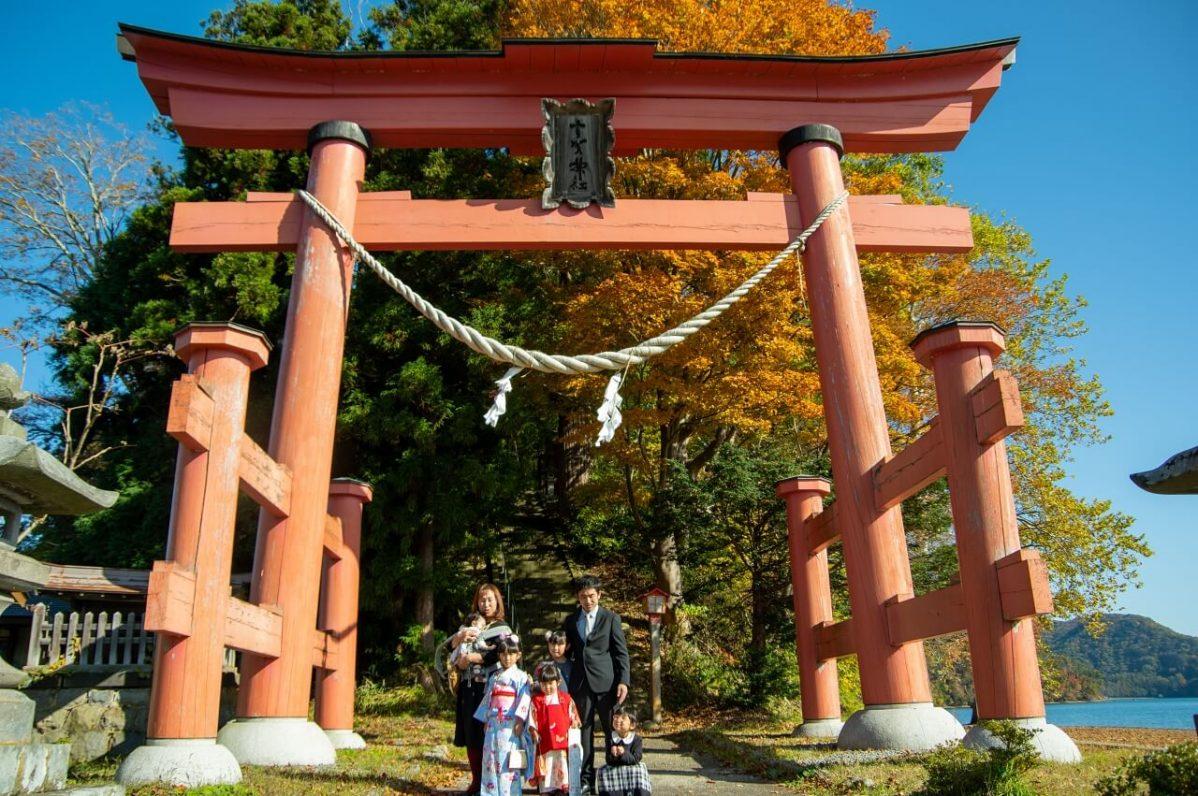 宇賀神社の鳥居の下で、七五三のお参りの記念撮影