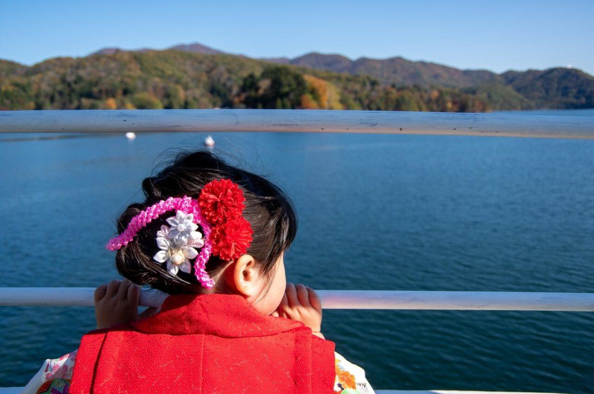長野県信濃町野尻湖の宇賀神社へ向かう遊覧船から、少女が湖を見ているところ